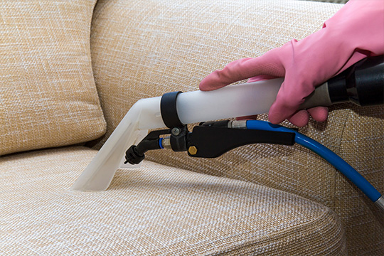 Person with pink glove cleaning sofa