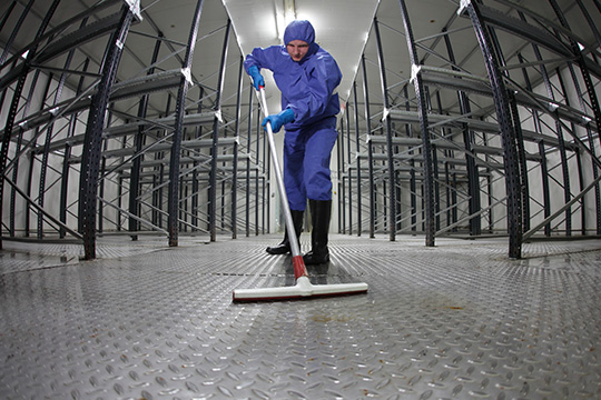 Man in blue overalls mopping floor