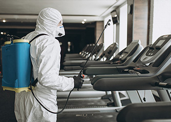 Man in full cleaning gear cleaning a gym
